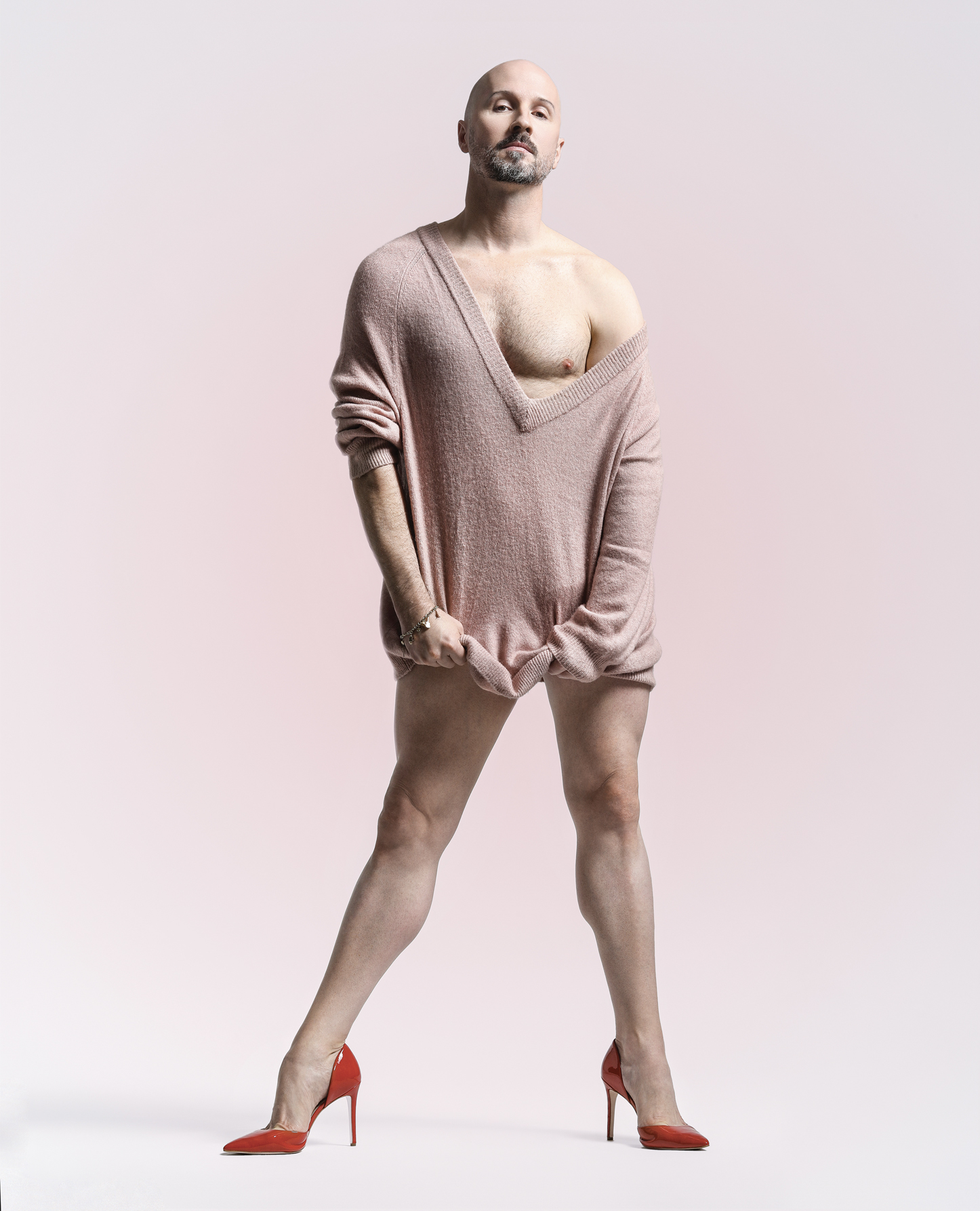Robert Curran in a sweater and red high heels.