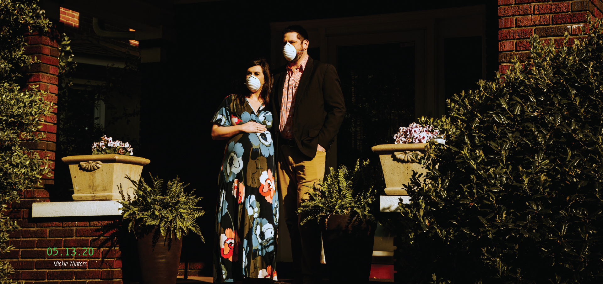 A pregnant couple standing on their porch wearing masks. 05.13.20, by Mickie Winters