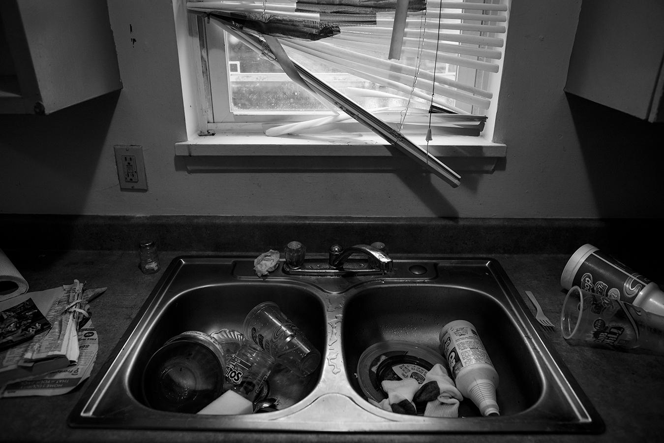 Broken blinds above a garbage-filled sink.