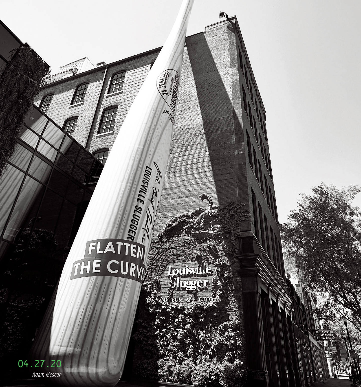 """The bat outside Louisville Slugger Museum, with a sign reading, """"Flatten the curve."""" 04.27.2020, by Adam Mescan"""